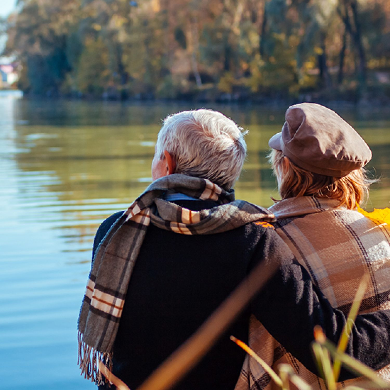 Senior couple relaxing by autumn lake. Happy man and woman enjoying nature and hugging sitting on pier.